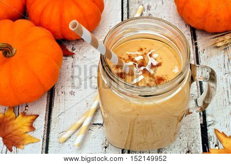 Pumpkin Smoothie In A Mason Jar With Coconut And Cinnamon, Scene On Rustic White Wood