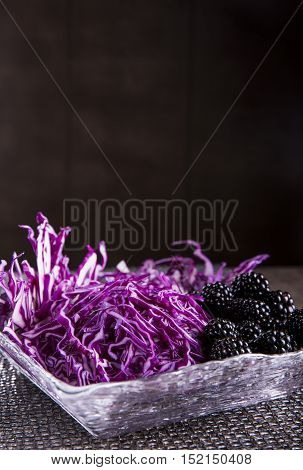 salad of red cabbage and blackberry on a dark background