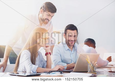 Happy workers. Picture of young office workers sitting with laptop at desk and man standing behind them.