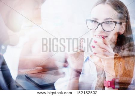 Distance relationships. Dreamy pretty girl with glasses holding white cup and intently looking at transparent silhouette.