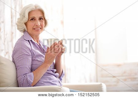 Cheerful mature lady is relaxing with hot tea in the morning. She is sitting on armchair and holding cup. Lady is looking at camera and smiling