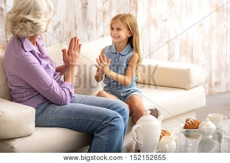 I like this game. Cheerful girl is having fun with her granny. They are clasping hands and smiling. Family is sitting on sofa
