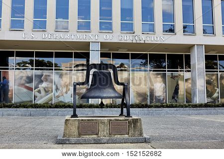 Washington DC USA - October 1 2016: Department of Education building with sign and windows of government offices including a mural of students on the windows and Milford School Bell in the front of building representing the goal to educate