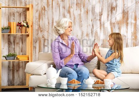 Happy old woman is playing with her granddaughter at home. They are sitting on couch and clasping hands. Family is laughing