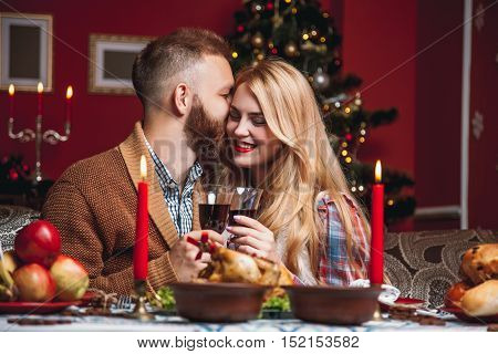 Beautiful Couple In A Decorated Festive Interior With A Christmas Tree Drinking Wine. A Romantic Din