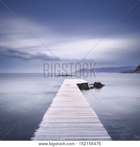 Wooden pier or jetty in the bay rocks and sea on misty sunset. Long Exposure