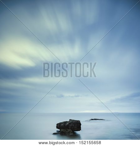 Dark rocks in a blue ocean under cloudy sky in a bad weather. Long exposure photography