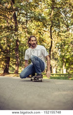 Skateboarder Squatting On A Skate And Ride Through The Forest