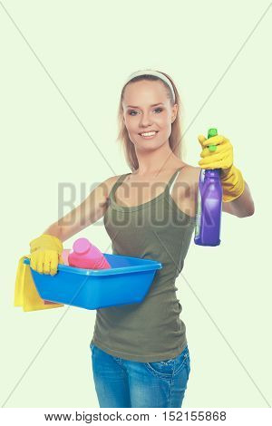 Cheerful woman is cleaning something with wisp and spray attentively