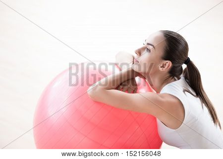 Looking into the distance. Attractive thoughtful young woman resting her hands on a fitness ball and looking somewhere while having a break during a workout