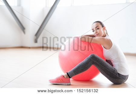 Need to take a break. Beautiful hard working brunette woman sitting on the floor and leaning on a fitness ball while having a break