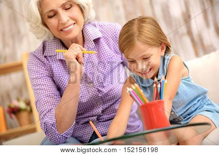 Joyful family is entertaining at home together. Small girl is coloring picture with interest. Her granny is sitting and looking at image and smiling