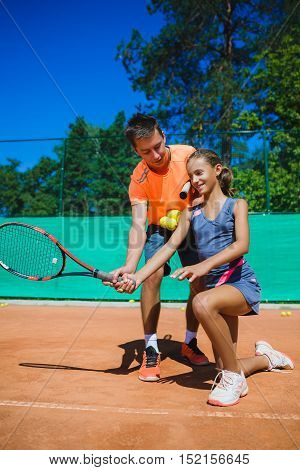 Instructor or coach teaching child how to play tennis on a court indoor.
