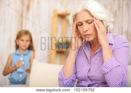 Old woman is suffering from headache. She is sitting on sofa and touching head with frustration. Worried girl is standing behind her and holding water