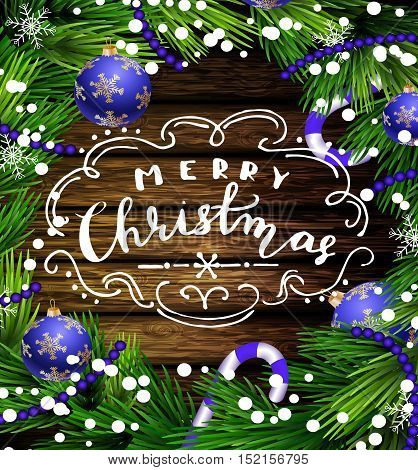 Christmas New Year design wooden background with christmas decorations candy canes snow and balls arranged in a frame and with handwritten Merry Christmas