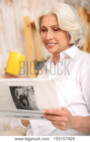 Joyful mature woman is relaxing with cup of tea. She is reading newspaper and smiling