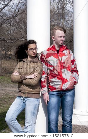 Girl with glasses and a guy waiting in a red jacket