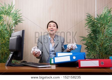 Woman under stress tossing papers in the office