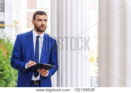 luxury man in blue suit writing outdoors and looking into the distance