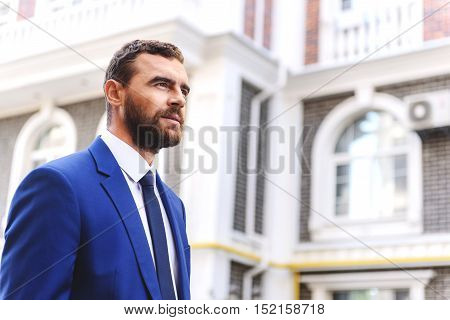 confident businessman in outfit standing on the street, selective focus