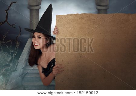 Pretty Young Asian Woman Dressed As A Witch Holding Parchment Board