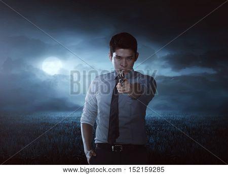 Asian man aiming gun on the meadow field