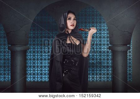 Young Beautiful Asian Witch Holding Bloody Knife