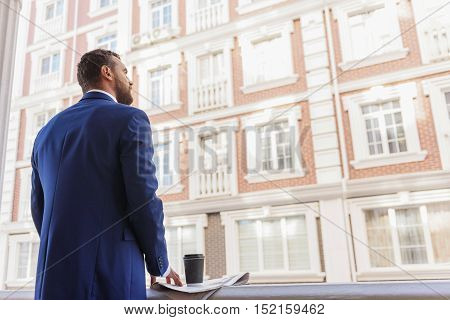 back view of a successful businessman looking into the future with copy space