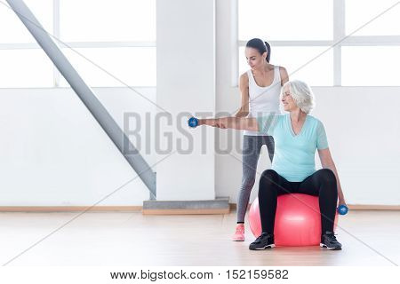 Various sports equipment. Pleasant confident slim woman holding blue rubber dumbbells and smiling while sitting on a fitness ball