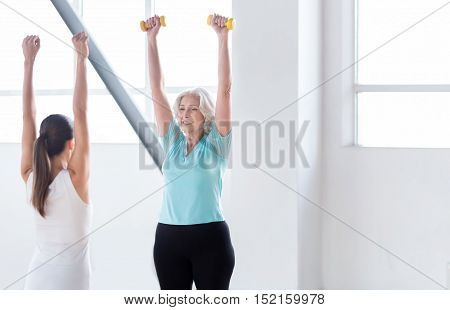 Healthy way of life. Pleasant well built old woman standing opposite her fitness coach and holding her dumbbells up while repeating after her