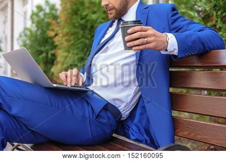 elegant businessman sitting in a park with a laptop and working