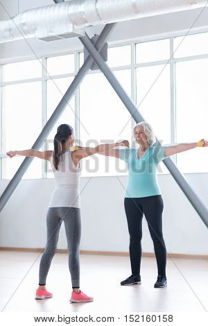 Need to do it right. Happy energetic active woman raising her arms sideward and smiling while exercising together with a fitness coach