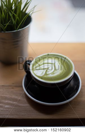 a cup of green tea latte on table