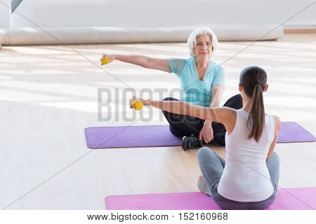 Calmness and peace. Good looking peaceful grey haired woman sitting cross legged on a yoga mat opposite her coach and holding a yellow dumbbell