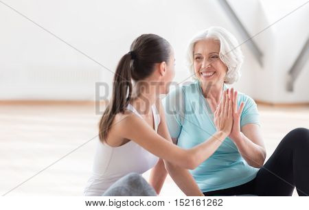 Give me the high five. Cheerful active confident women doing high five and laughing while relaxing after aerobics classes