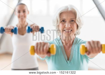 Exercises with dumbbells. Sporty active happy woman looking at you and smiling while exercising with dumbbells
