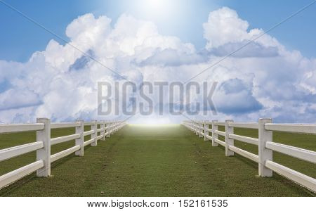 White concrete fence in farm field under blue sky
