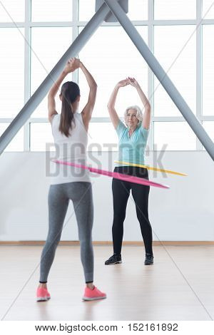 Getting a small waist. Active confident delighted women standing opposite each other and rotating hula hoops while working out in the fitness club
