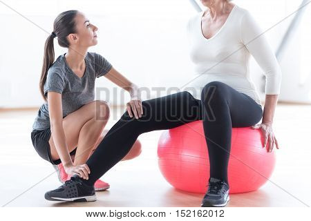 In the right position. Nice attractive skillful coach sitting near the woman and holding her leg while helping her with the exercise