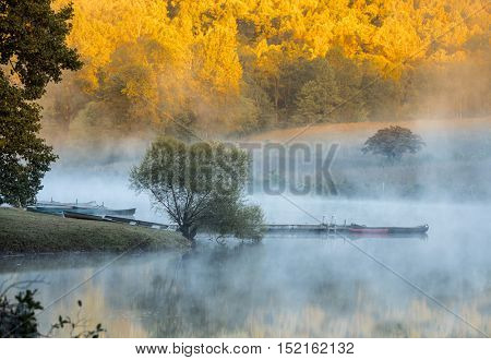 mist on the water with fall colors in background in North Carolina