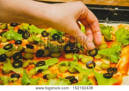 women hand prepare homemade rectangular pizza, ingredients close up