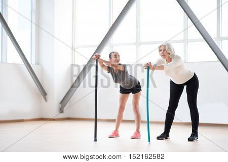 Involved in the workout. Confident delighted pleasant women using sports equipment and exercising while having fitness classes