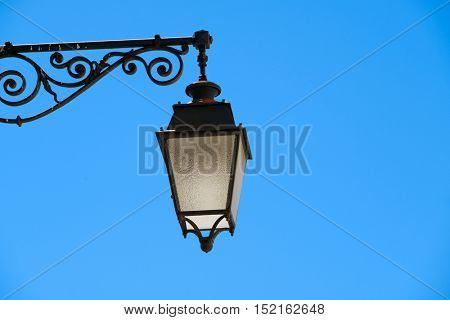 Retro vintage street light against blue sky