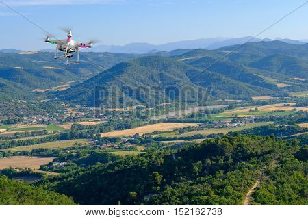 Quadcopter flies in countryside at Provence, France