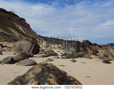 beach covered in rocks with cliff on side
