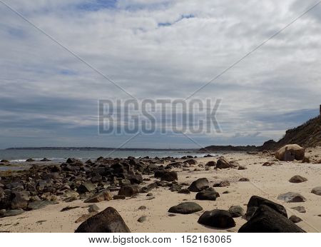 rock covered beach view with sand and sky