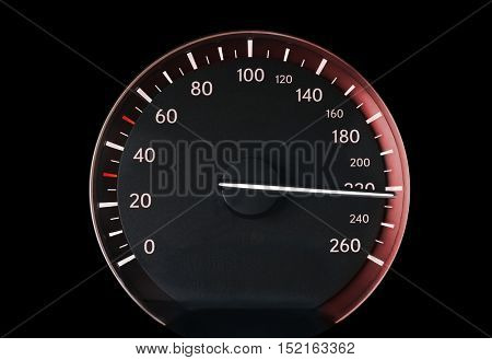 Speedometer of a car showing 220, glowing with red light