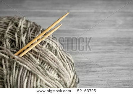 Ball of multicolored knitting yarn and needles on grey wooden background