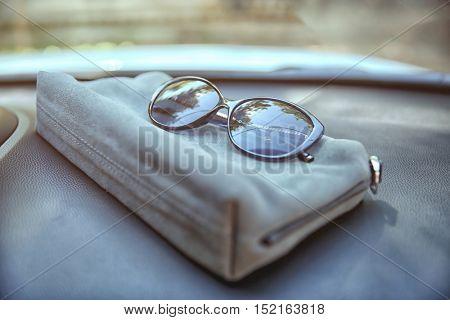 Woman bag with sunglasses on car panel, closeup