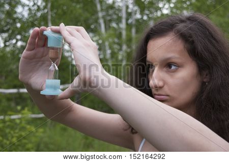 Girl holds in two hands in front of him hourglass